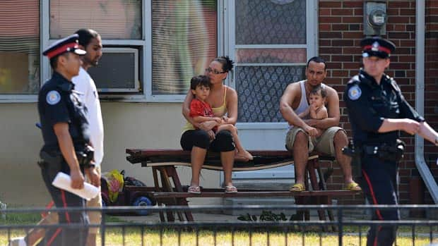 Neighbours who live near the location of the Danzig Street shooting watch as police walk by on July 17, the day after the shooting.