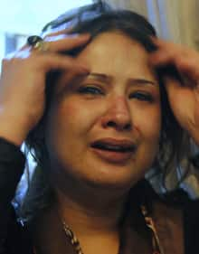Bruises are seen on the face of Iman al-Obaidi as she cries at the Rixos Hotel in Tripoli on March 26.