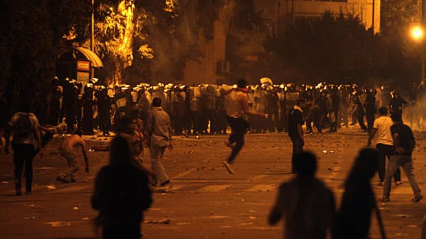 Egyptian protesters throw stones during clashes with security forces early Saturday next to the building housing the Israeli Embassy in Cairo.
