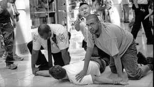 Security guards pin a man at Metrotown mall in an incident that led to a confrontation with the photographer.