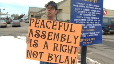 Donald Smith was protesting a sign at Glenmore Landing in Calgary's southwest Sunday that bans political demonstrations.