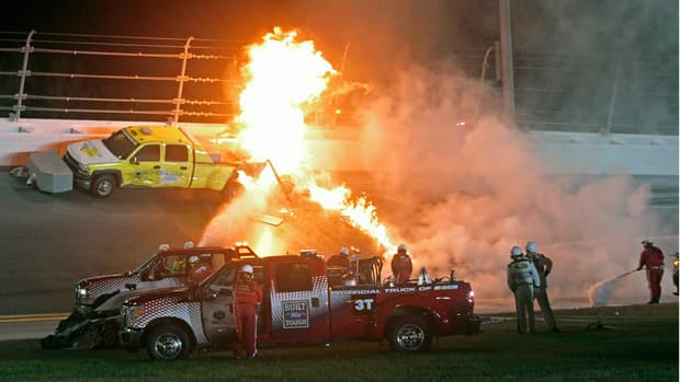 Emergency workers try to put out a fire after Juan Pablo Montoya's car struck the truck during the NASCAR Daytona 500 auto race at Daytona International Speedway in Daytona Beach, Fla., on Monday.
