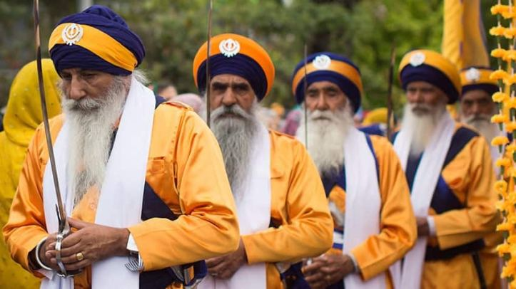 Sikh men with sabres celebrate Vaisakhi.