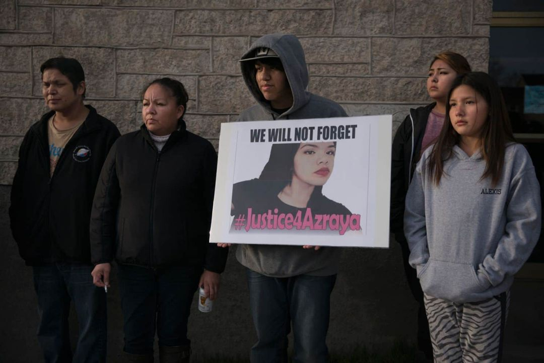 Azraya's father, Marlin Kokopenace, far left, her mother, Christa Ackabee, second from left, and her brother Braeden, holding the sign, were in Kenora that day. (Ed Ou/CBC)