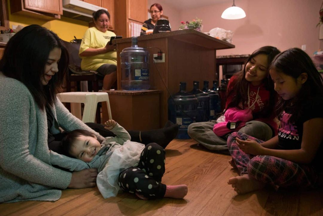 Kyra Sinclair, left, plays with her daughter while friends and family look on. (Ed Ou/CBC)