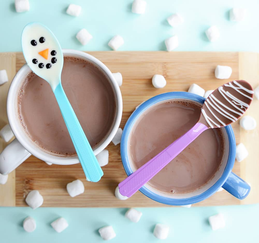 Two decorated spoons on mugs of hot chocolate.