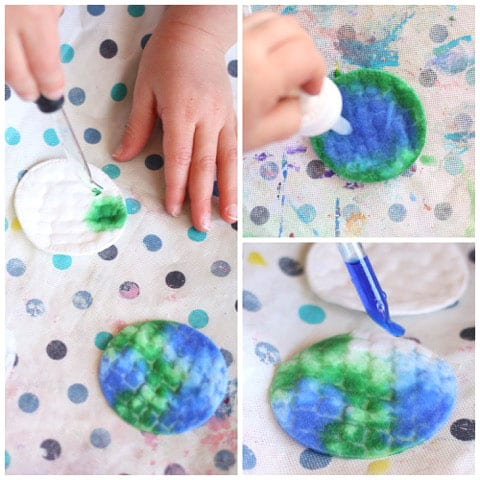 A collage of four images of kids using droppers to drop small amounts of blue and green paint onto round cotton makeup pads.