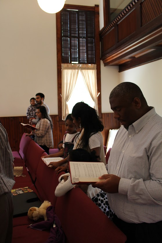 picture of family singing - our congregation