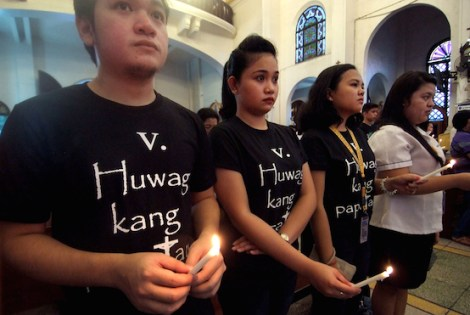 "Parishioners in Manila wearing black shirts with ""Thou Shall Not Kill"" prints light candles to remember those who died in the government's war against crime. (Photo by Angie de Silva)"