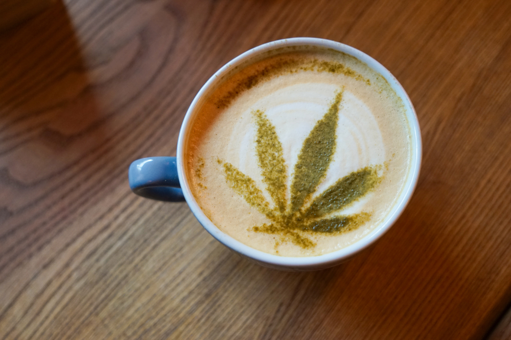 hemp leaf made out of cream in a cup of coffee
