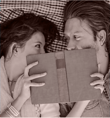 man and a woman using a book to cover their mouths while they whisper secrets