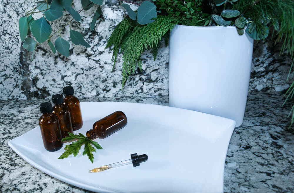 CBD Natural Plant Medicine derived from hemp to oil and cream combined with coconut white and grey granite background with brown amber glass bottle and dropper display