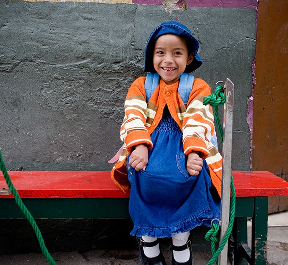 Photo of Bolivian child smiling on a bench