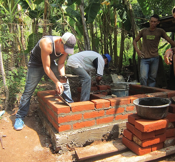 Photo of men laying bricks while building a house