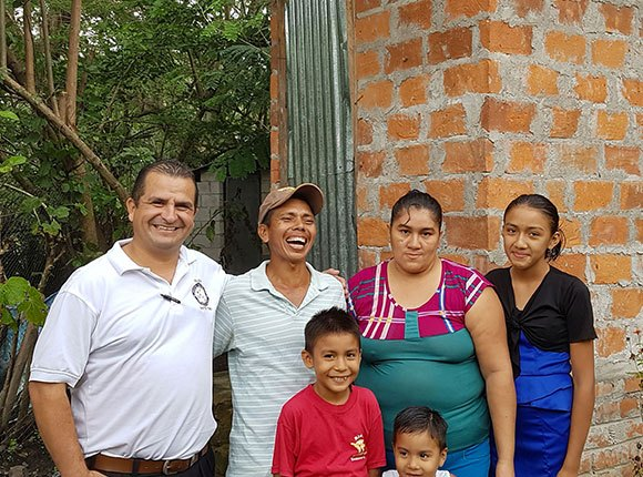 Photo of Salvadoran family with a pastor by a latrine