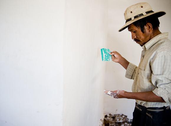 Photo of Bolivian man painting a wall