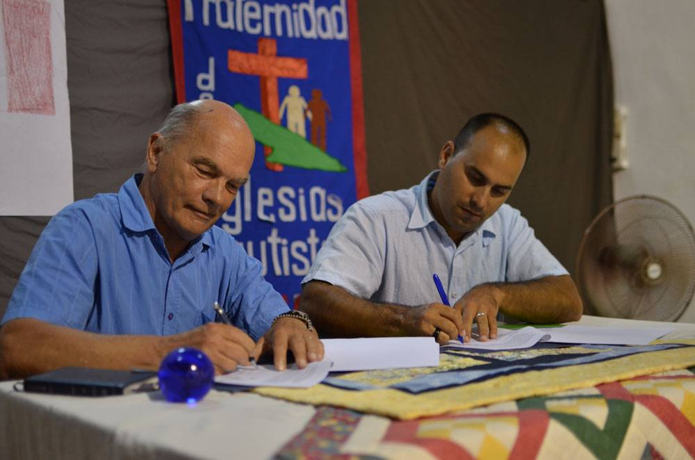 Photo of two men signing an agreement