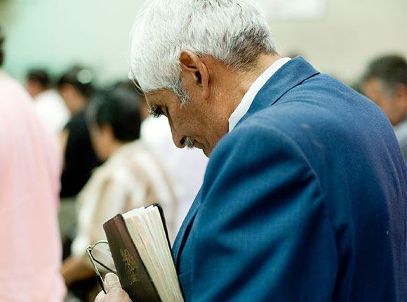 Photo of elderly man at church holding a Bible