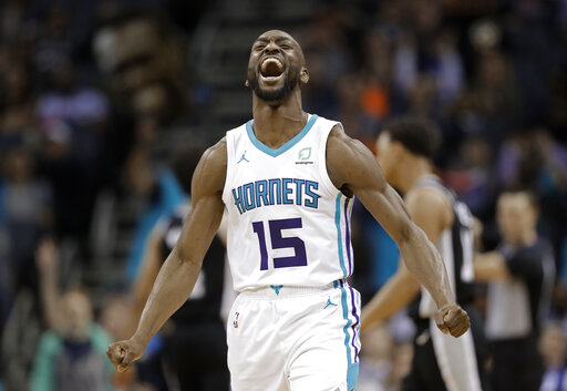 4e9025db75594 File-This March 26, 2019, file photo shows Charlotte Hornets' Kemba Walker  (15) reacting after making a basket against the San Antonio Spurs during the  ...