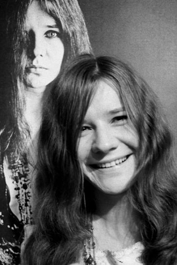 janis joplin smiling in front of a poster of her