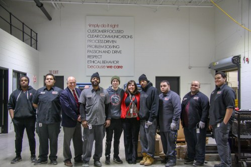 Mayor Clough and Director Boczek pose for a photo with the Conveyer & Caster assembly team.