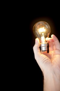 Lit light bulb in a hand