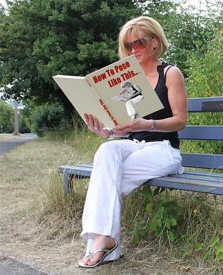 Woman sitting on bench in same pose as the woman on the cover of the book she is reading entitled