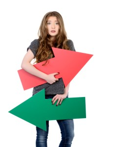 confused young woman with colorful arrows, casual clothes, blond hair, photo taken in studio shot on white background.