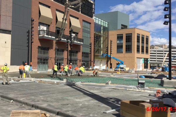 11construction workers building sidewalks in front of Little Caesar's Arena