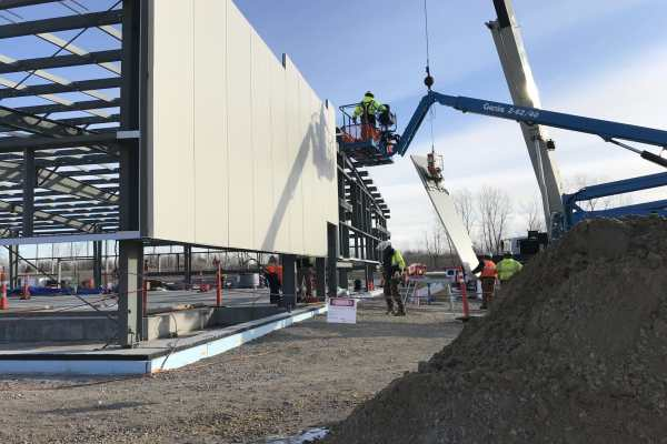 11workers attach wall panels on metal frame