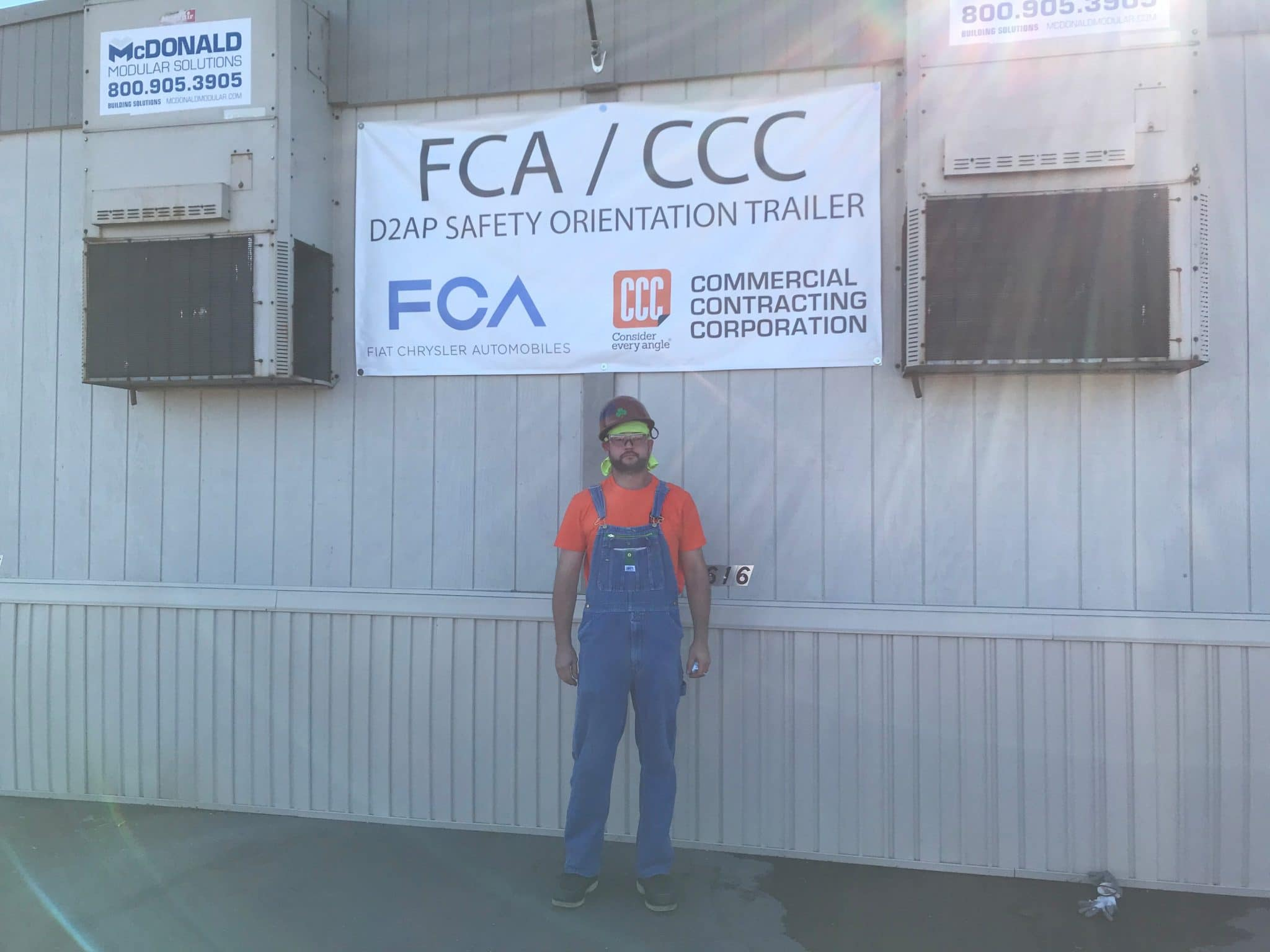man in overalls stands below FCA/CCC sign