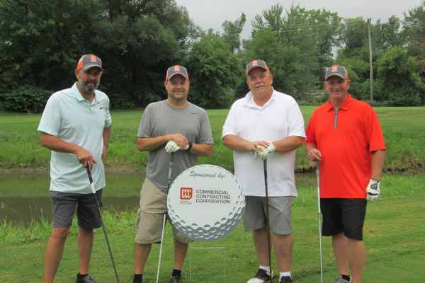 four men stand with golf clubs