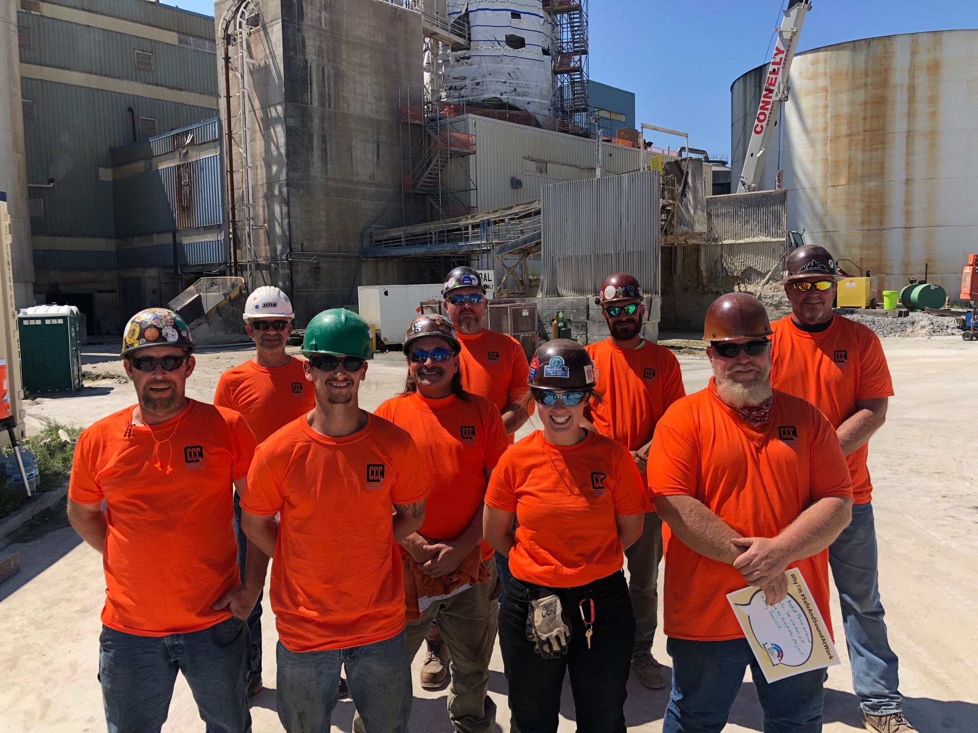 construction worker group photo in orange shirts