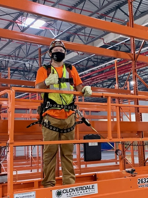 construction worker stands on orange scaffolding