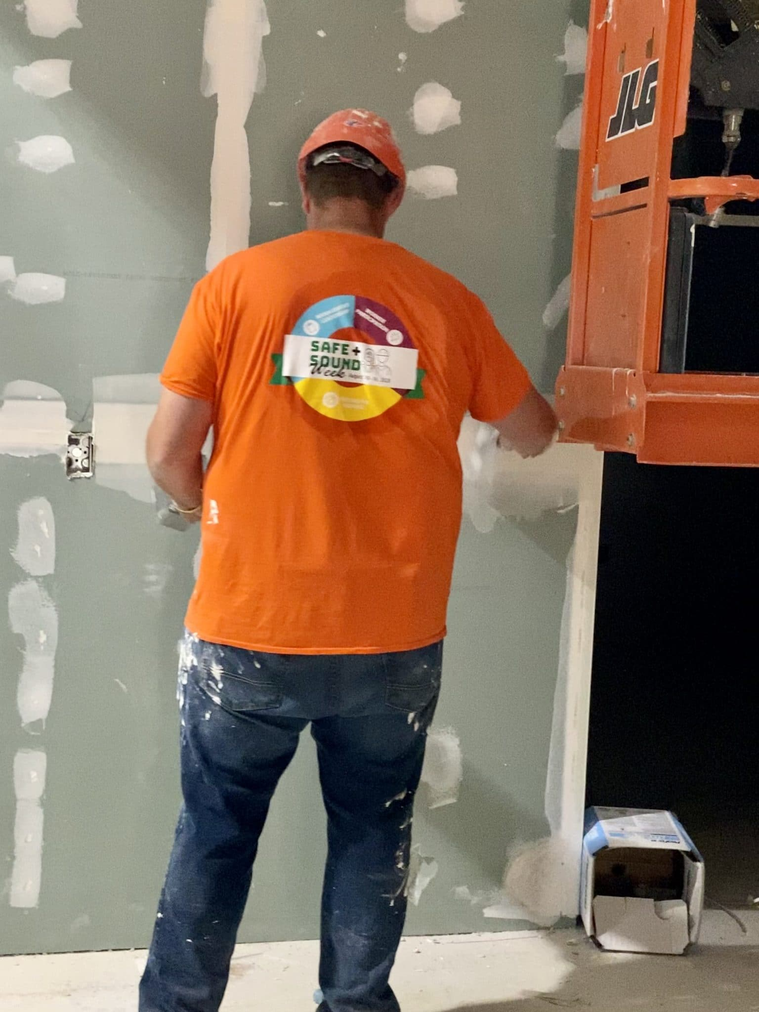 construction worker in orange shirt plasters wall