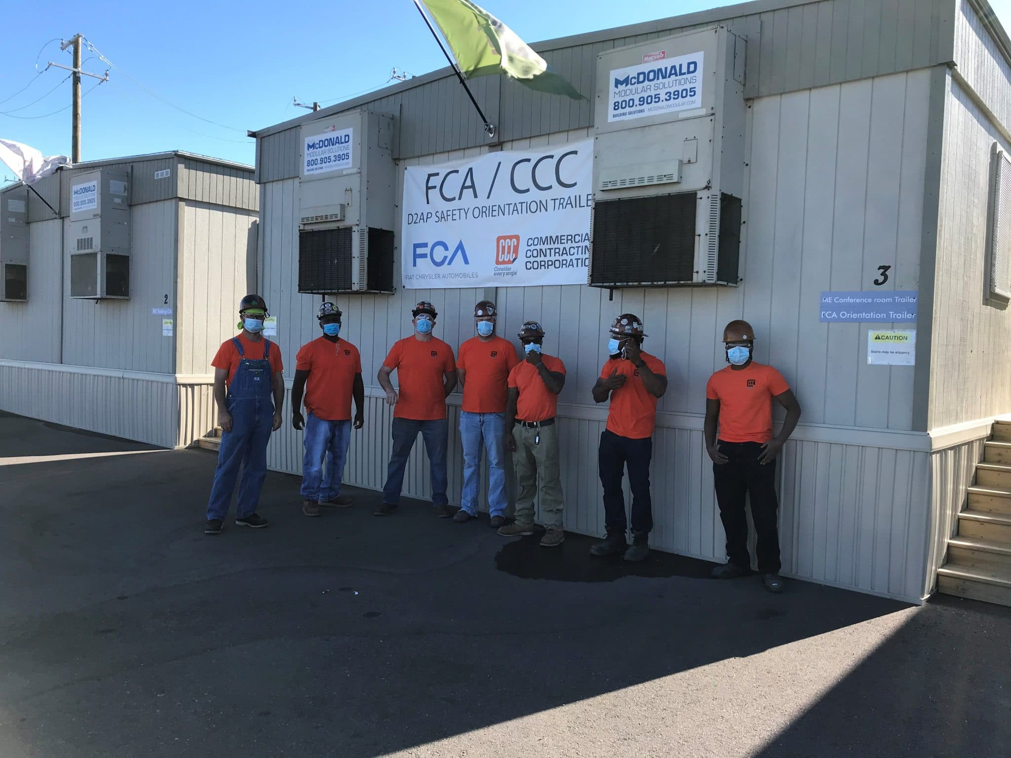 workers in orange shirts stand against trailer