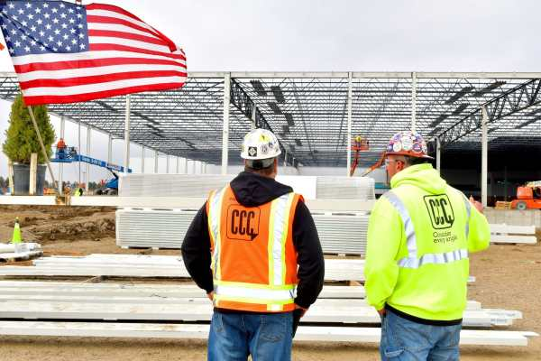 two construction men next to american flag