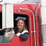 Female trucker in red semi-truck