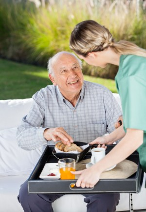 Female Caretaker Serving Breakfast To Senior Man