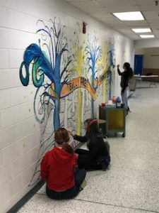 students painting the wall in the hallway