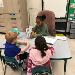 Elementary student reading to two primary students at a table