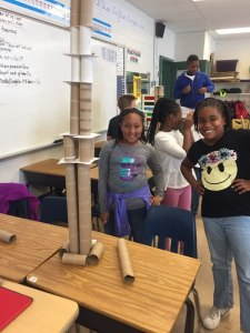 Two students smiling beside their tower project