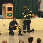 Firefighters showing students how they get low to the ground