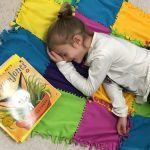 Student laying on blanket with a book