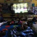 Students laying on floor watching a forest scene on the screen