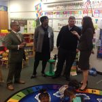 Adults talking while PreK students on iPad