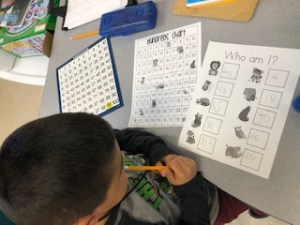 Student completing work with 100 chart