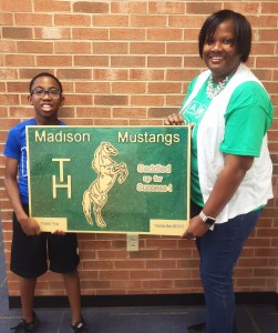 Fifth grade student presenting Mrs. Haley with Mustang plaque