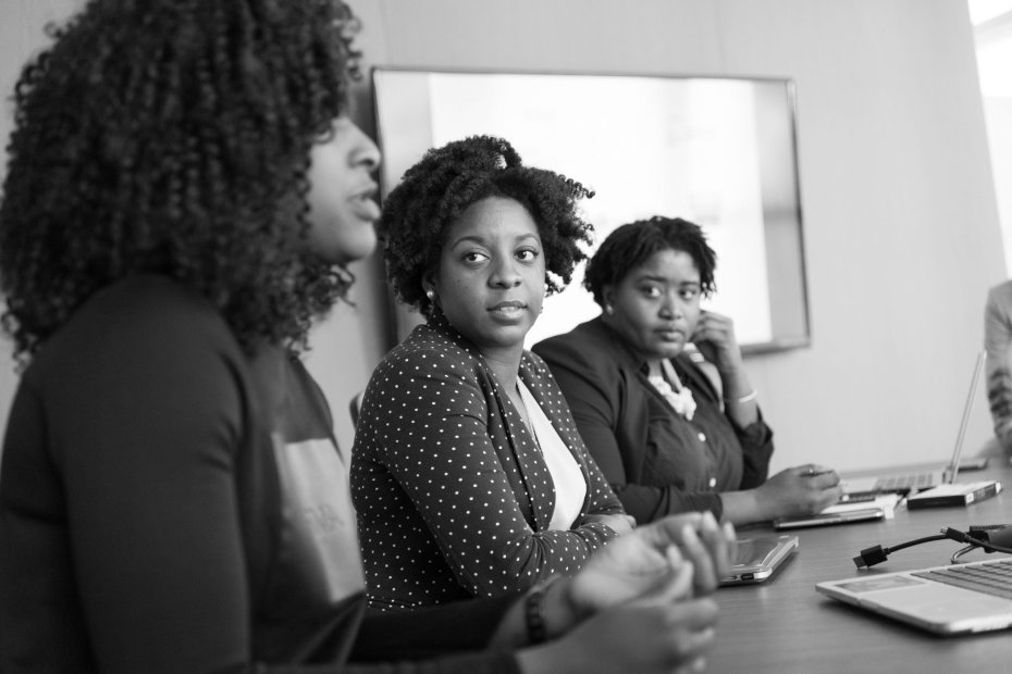 Women discussing around a boardroom