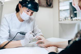 nail technician and customer both wearing a mask